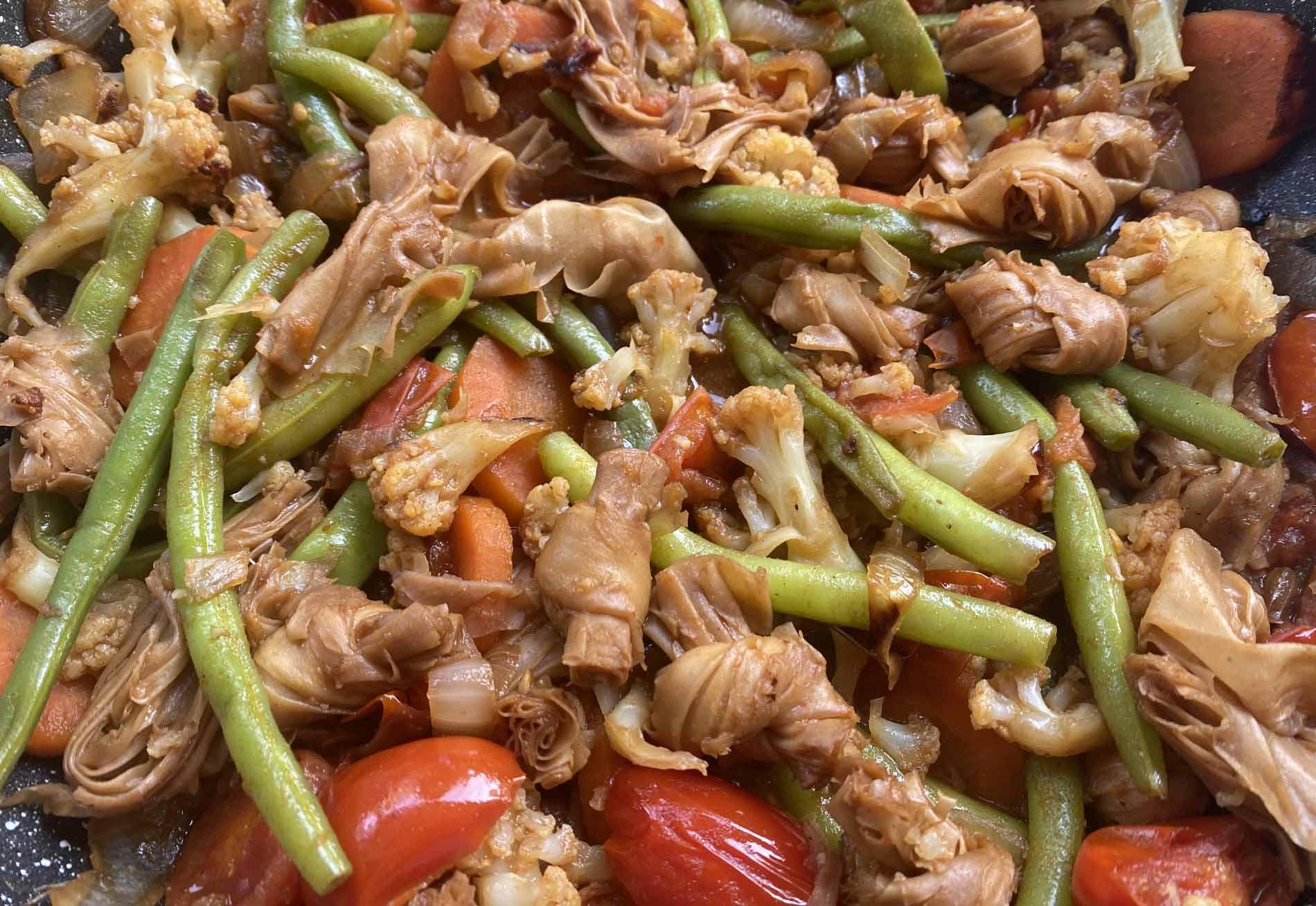 תקריב של ירקות מוקפצים עם פתיתי סויה
