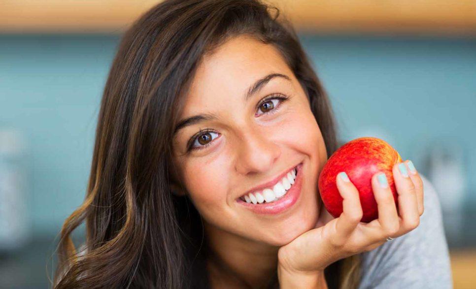 דיאטה טבעונית - אישה מחזיקה תפוח